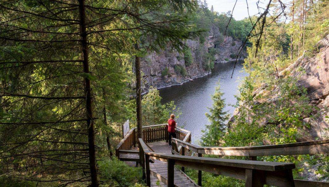 Person står på plattform med utsikt över sjö. Foto.