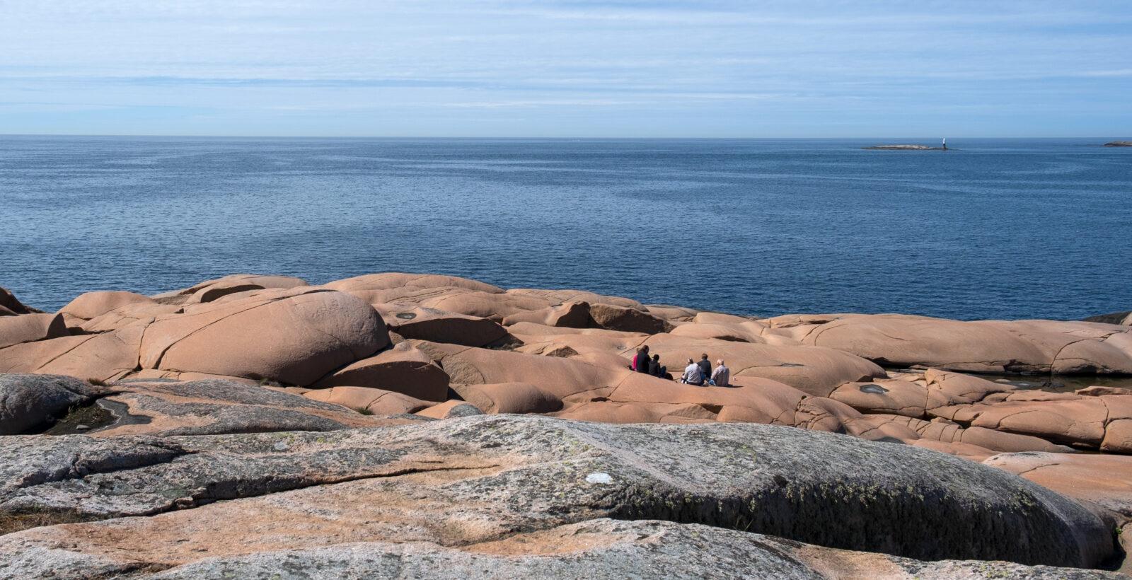 En grupp personer sitter och fikar på rosa klippor. Foto.