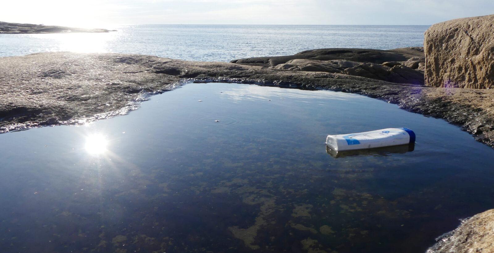En schampoflaska i havet. Foto.