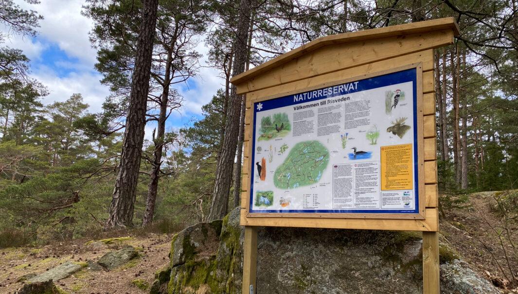 Foto på en skylt om naturreservaten i Risveden.