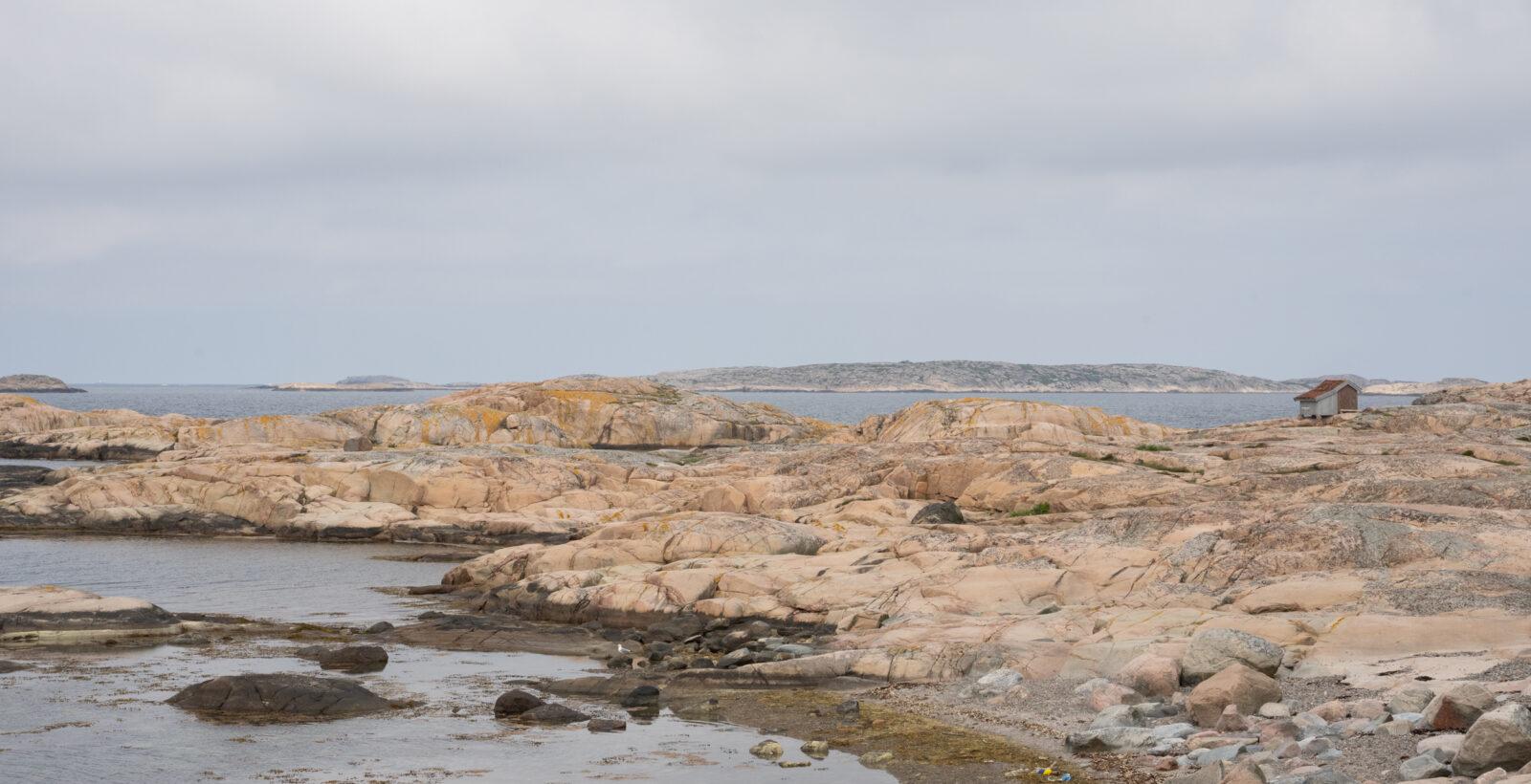 Klippor, hav och en liten bod. Foto.
