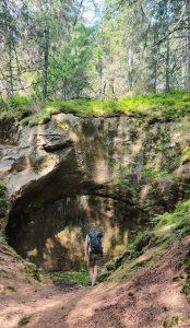 Foto på en person som står vid en bergvägg som har en stor rund urgröpning, en halv jättegryta.