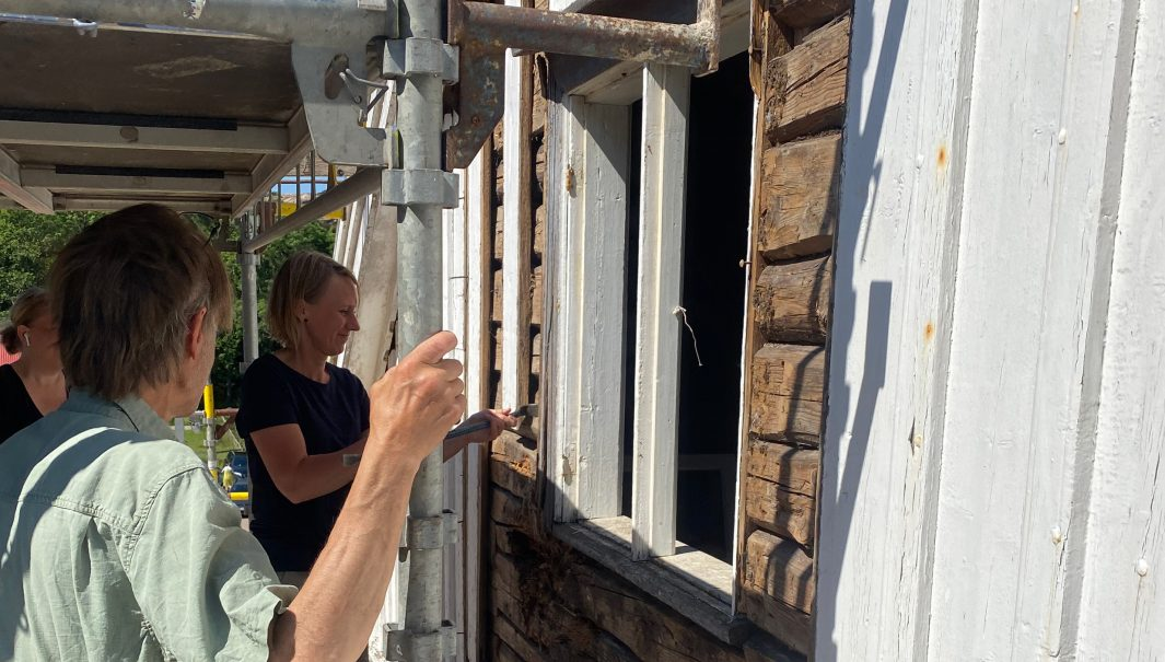 Personer står vid nyrenoverad fönsterkarm. Foto.