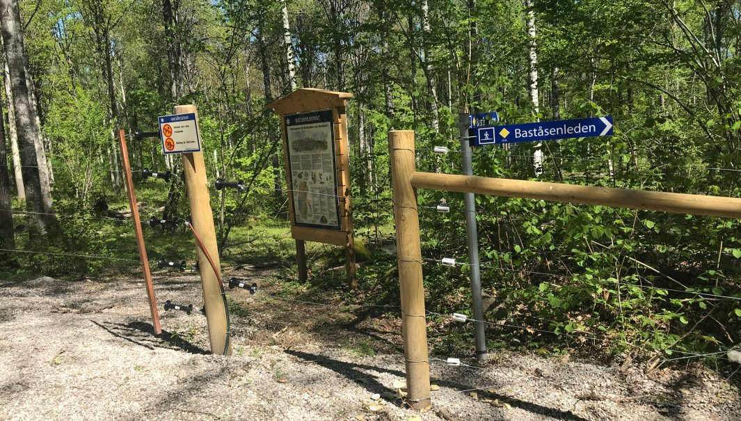 Stängsel, en stolpe med stigvägvisare på och ett skyltställ med en skylt om naturreservatet Baståsen. Foto.