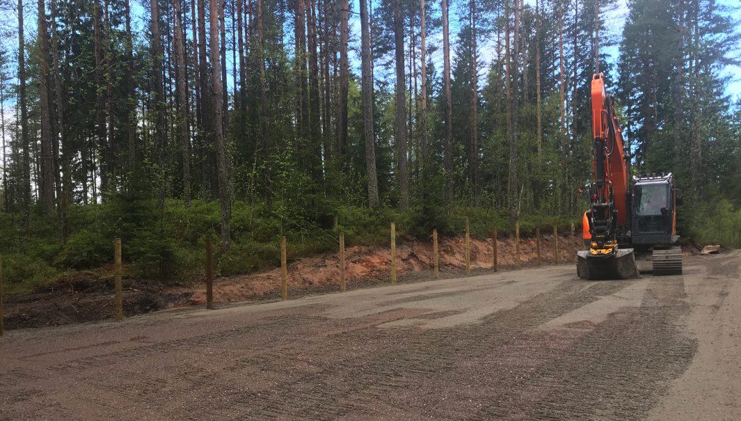 Grävmaskin på nyanlagd grusparkering. Foto.