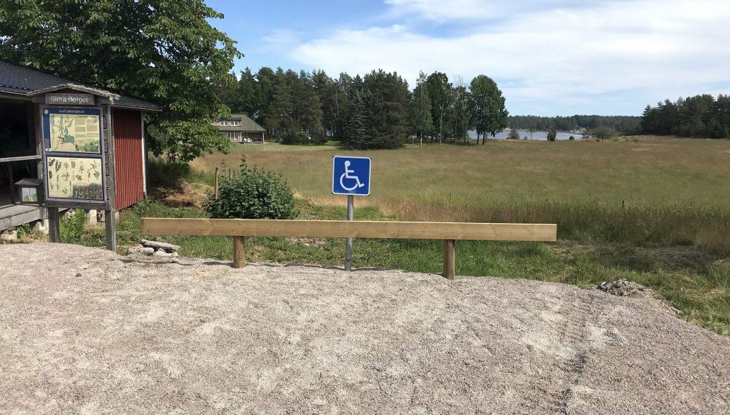 Grusad parkering med en reservatsskylt bredvid, samt utsikt över ängsmark och sjö. Foto.