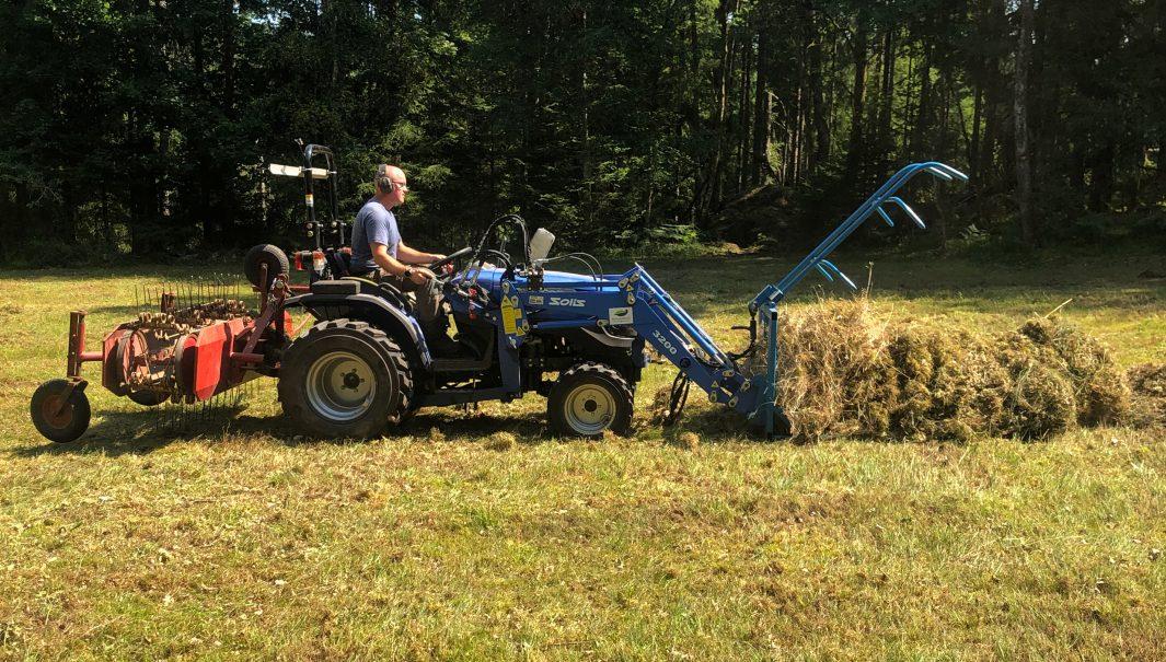 Person sitter på traktor och forslar bort hö.