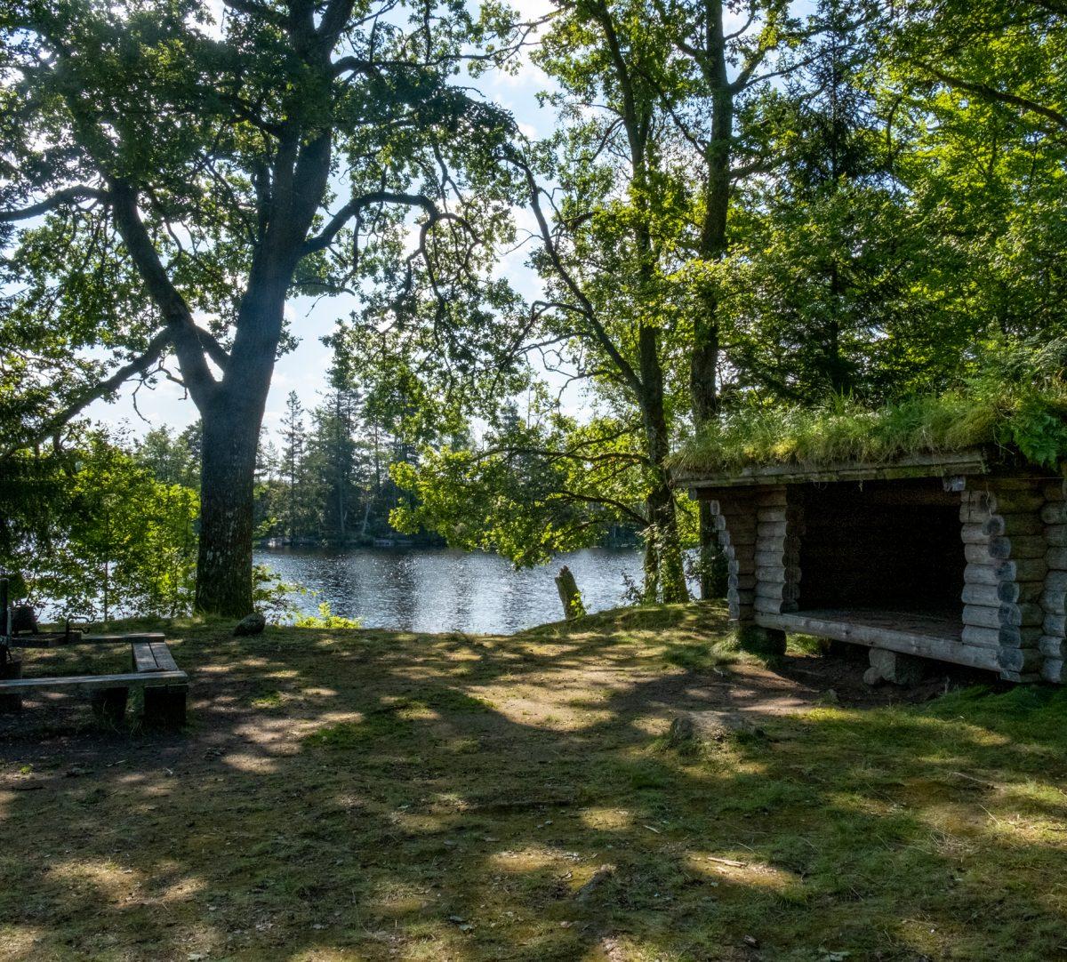 vindskydd med en eldstad en bit ifrån, vid en sjö. Foto.