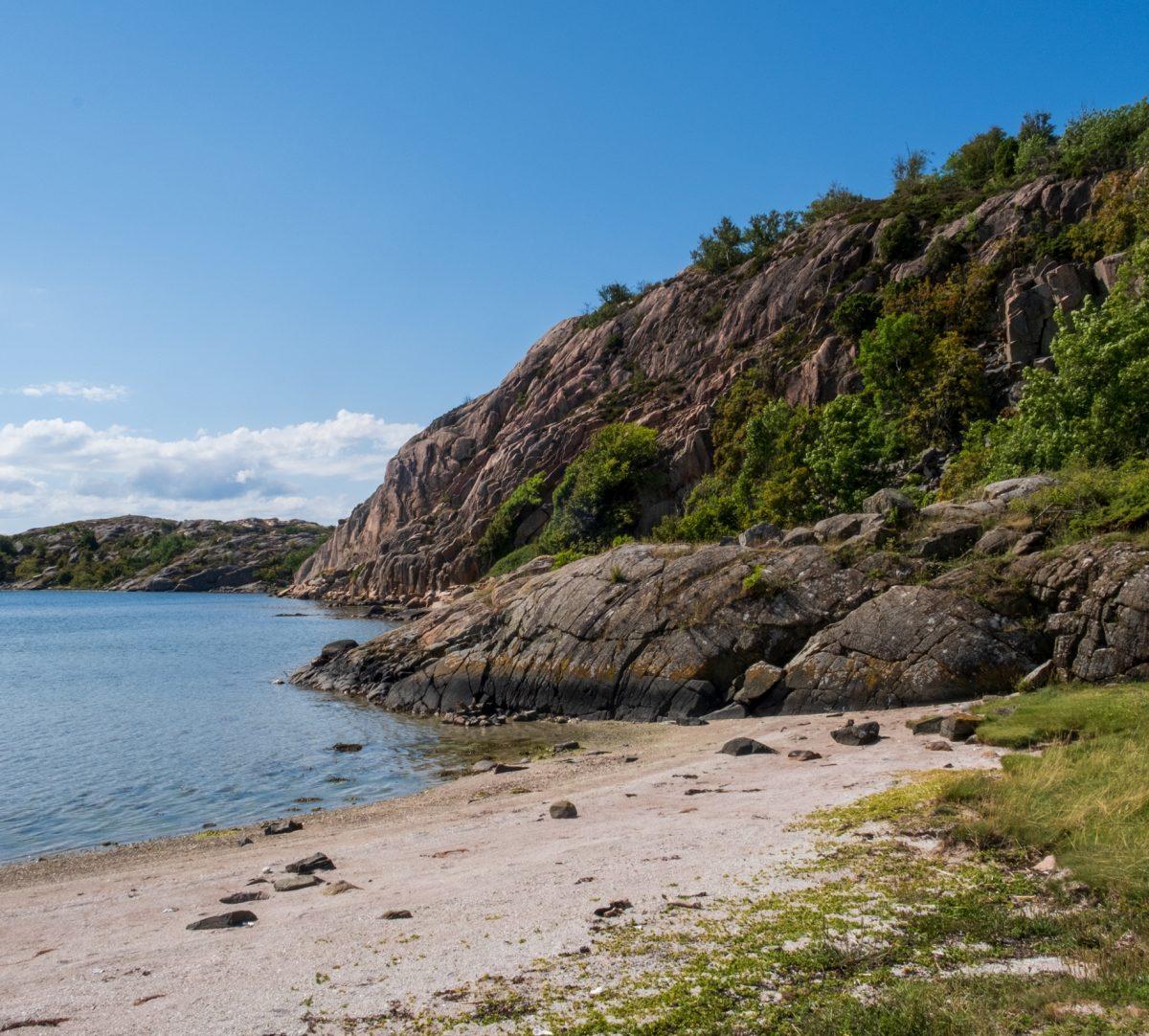 Rosa klippor, sandstrand och hav. Foto.
