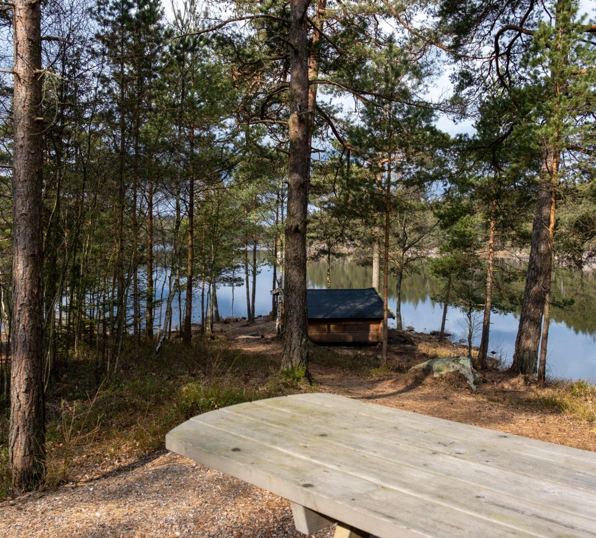 Bänk och ett vindskydd vis en sjö. Foto.