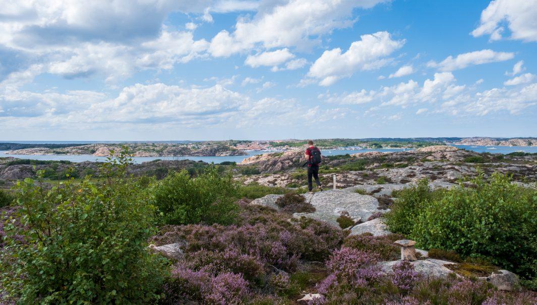 Person går längs med stig med utsikt över hav och granit. Foto.