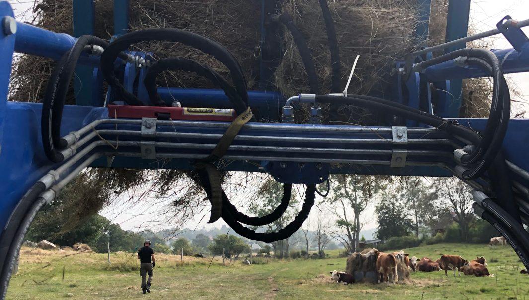 Traktor med en gripklo fylld med hö. Vy frön förarsidan. Foto.