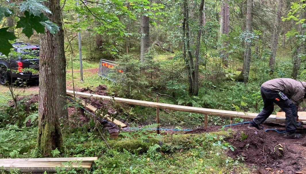 Person som bygger bro över en å: Foto.